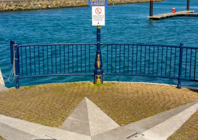 Compass points on ground with sign advertising boat trips, Bangor, Northern Ireland