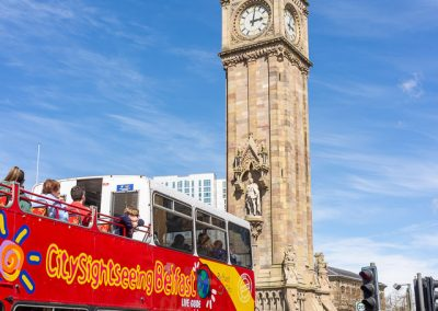 A Belfast Hop On, Hop Off tour bus approaches the Albert Memorial Clock