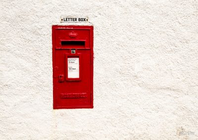 Postbox in a white wall