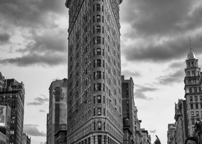 New York Bus Tour with the Flatiron Building. The Flatiron Building, originally the Fuller Building, was completed in 1902. It sits on a triangular block formed by Fifth Avenue, Broadway, and East 22nd Street
