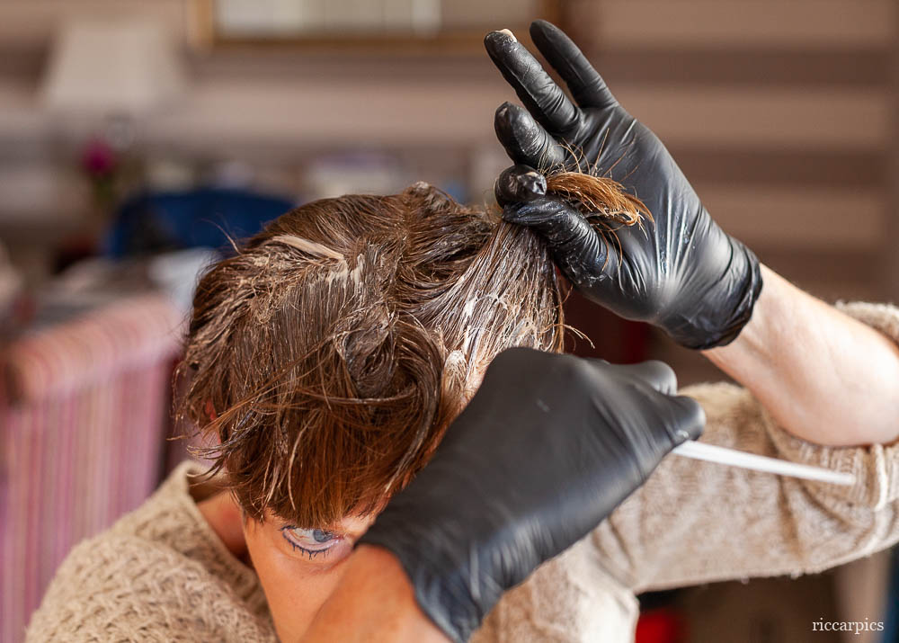 With hair dressing salons closed during the Corona Virus crisis a woman dyes her hair at home