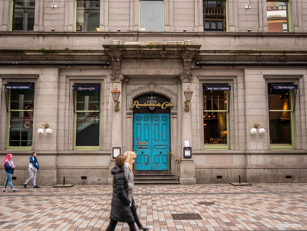 Two girls wearing masks walk past Revolucion de Cuba restaurant, Arthur Street, Belfast, Northern Ireland